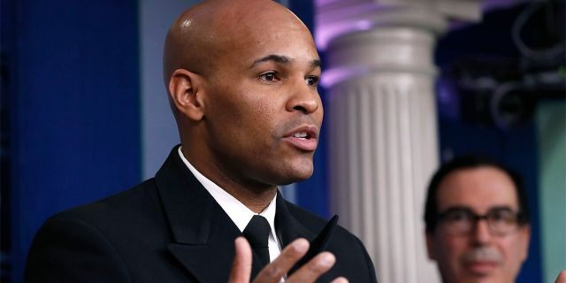 U.S. Surgeon General Jerome Adams speaks during a briefing on coronavirus in the Brady press briefing room at the White House, Saturday, March 14, 2020, in Washington, as Treasury Secretary Steven Mnuchin listens. Adams has said in no uncertain terms that any coronavirus vaccine distributed to Americans will be safe and effective. (AP Photo/Alex Brandon)