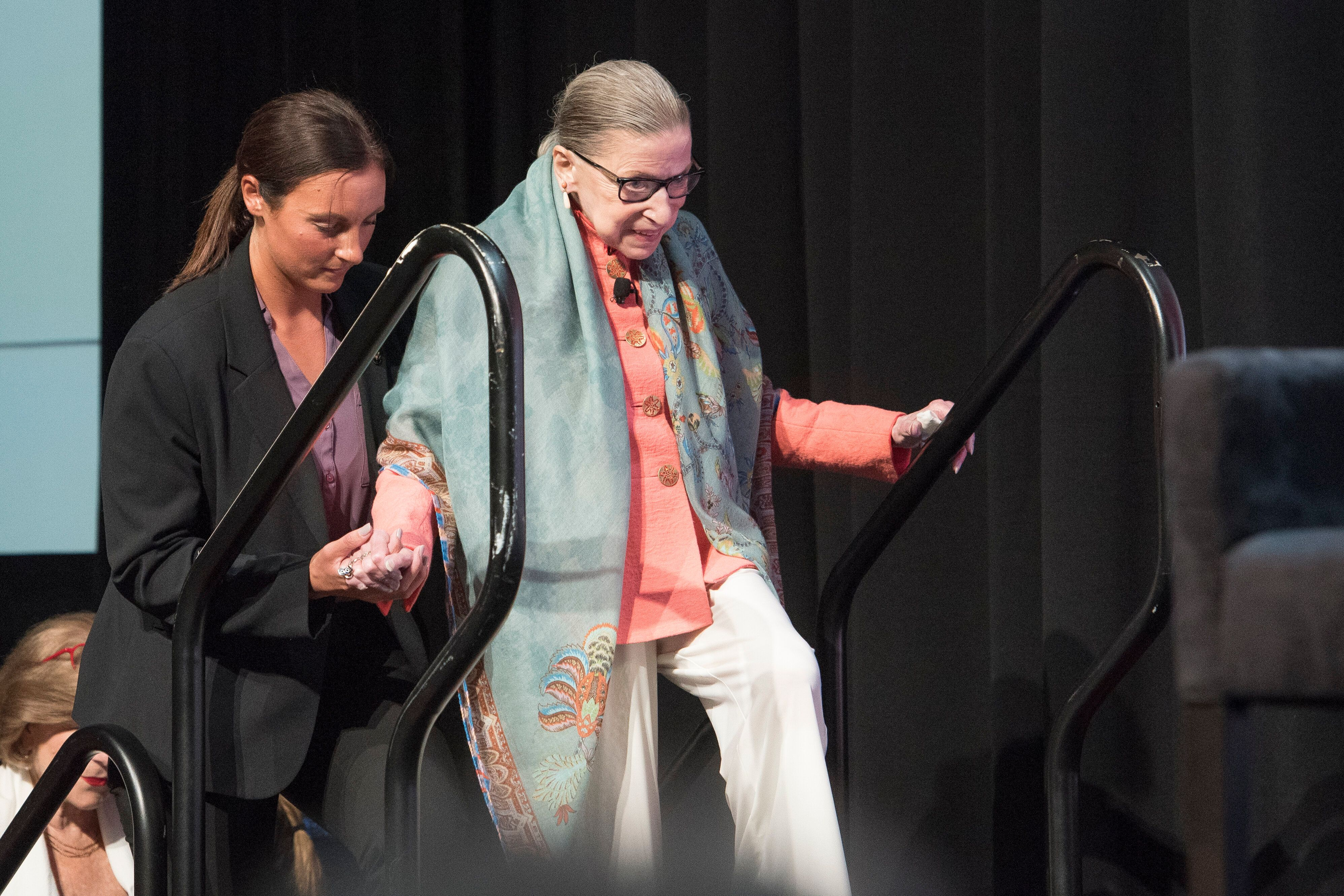 Supreme Court Associate Justice Ruth Bader Ginsburg is aided by a member of her security detail, as she walks up a set of sta