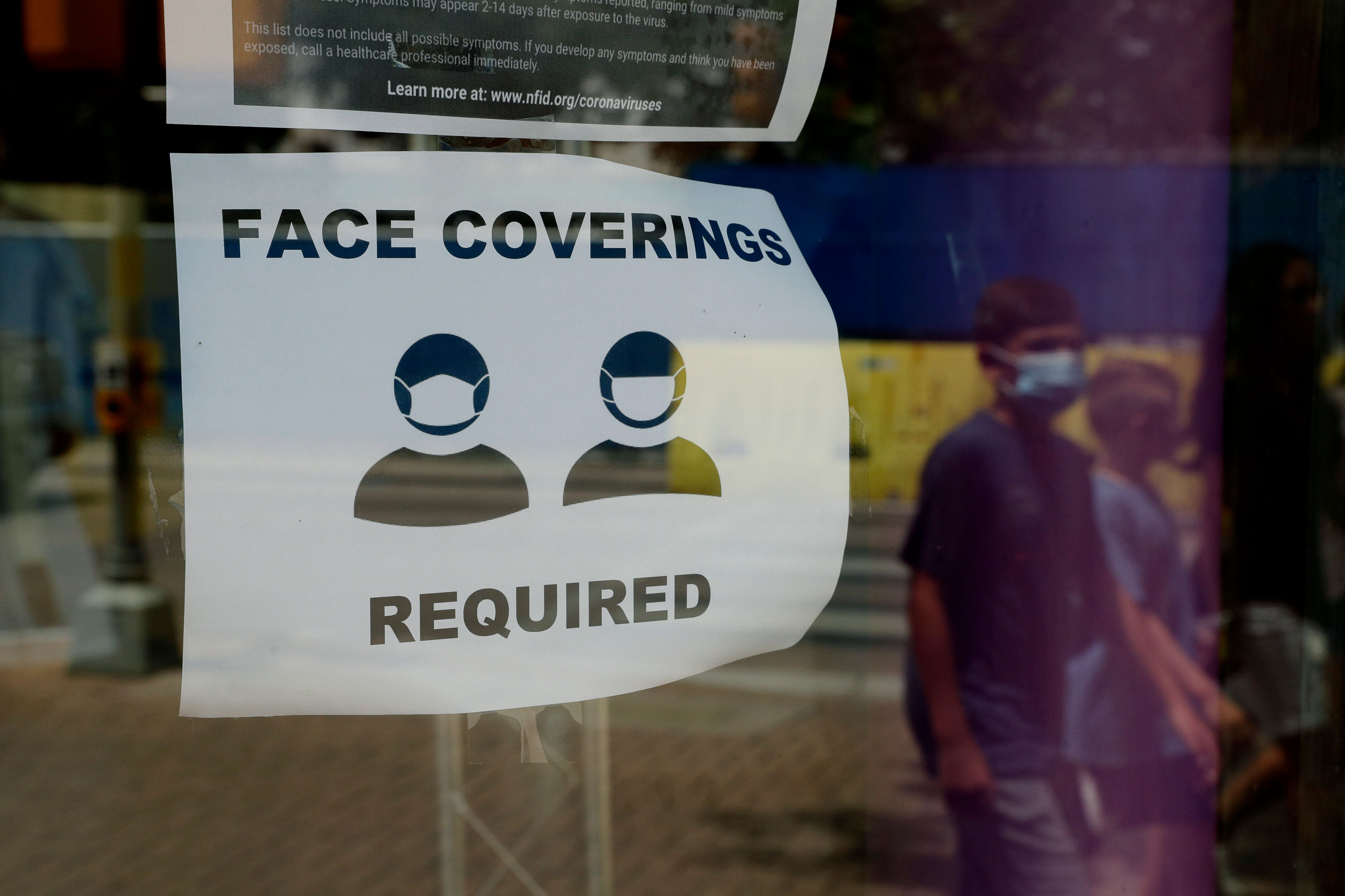 A visitor wearing a mask to protect against the spread of COVID-19 passes a sign requiring masks in San Antonio, Texas.