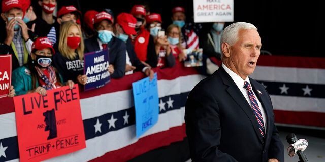 "Vice President Mike Pence gives a television interview after a campaign rally, Tuesday, Sept. 22, 2020, at Lanconia Municipal Airport in Gilford, N.H. where he praised the president's ""early action"" on the coronavirus pandemic. (AP Photo/Robert F. Bukaty)"