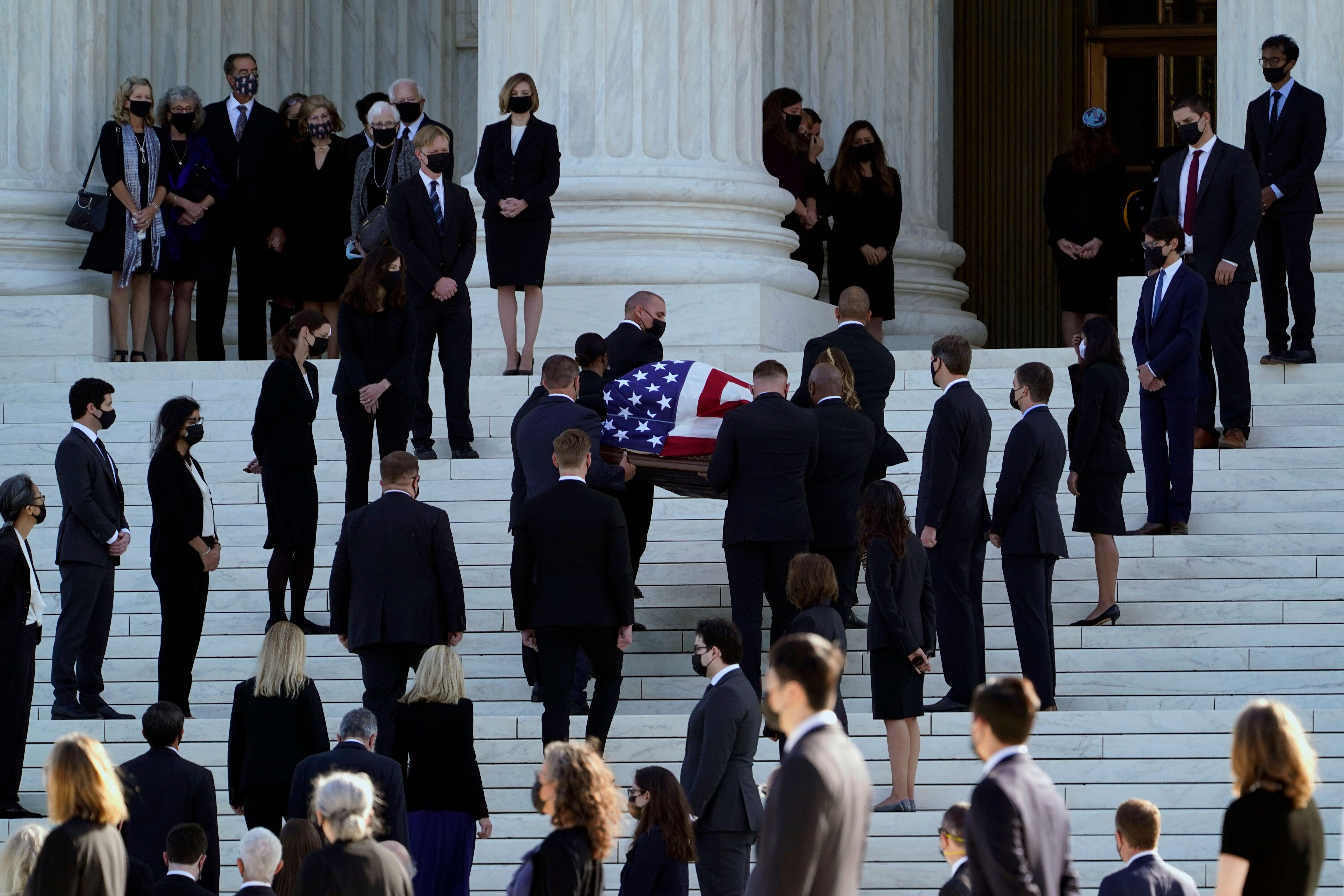 The flag-draped casket of Justice Ruth Bader Ginsburg is carried up the steps of the Supreme Court in Washington, Wednesday,