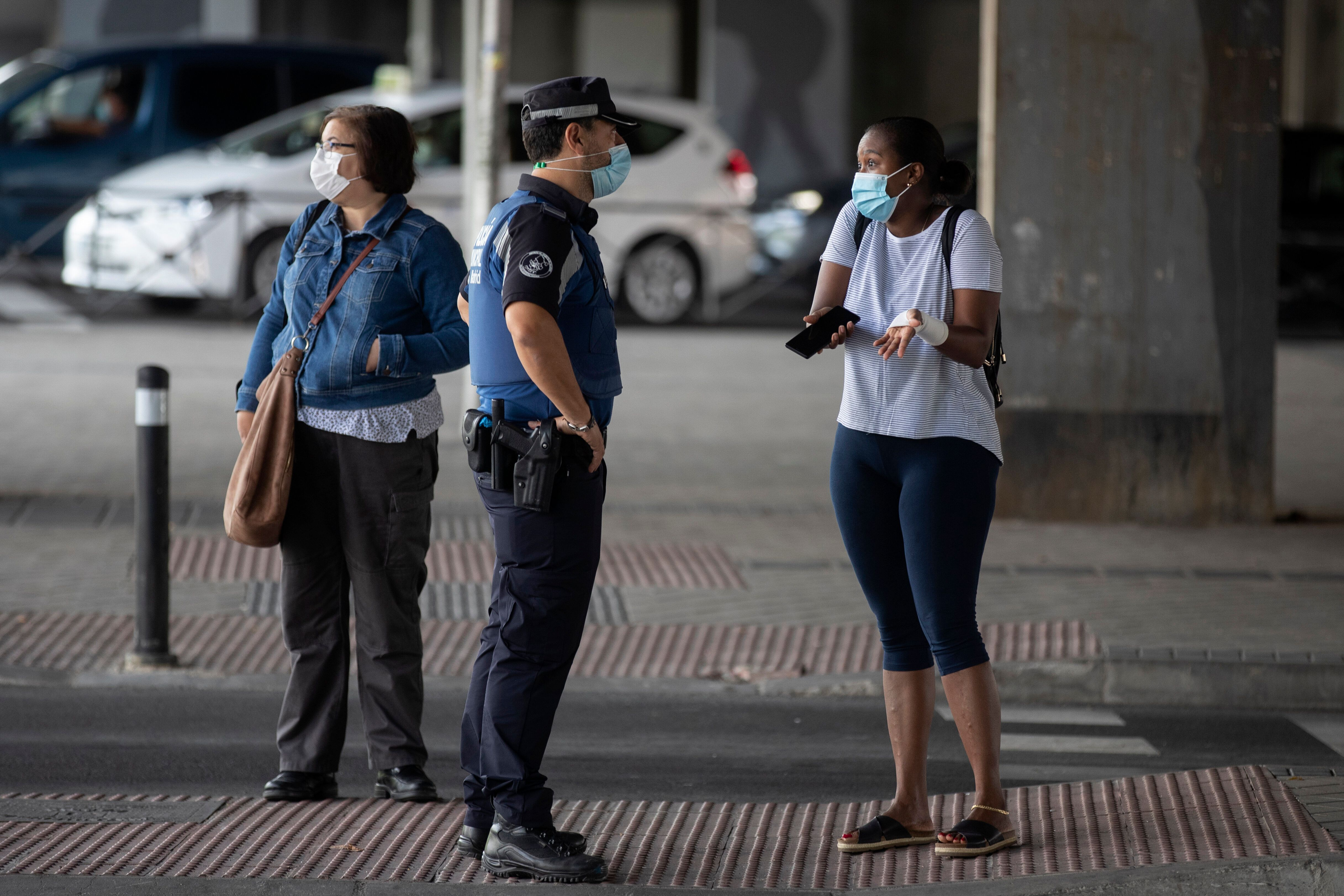 A local police officer talks with a woman at a checkpoint in the Vallecas neighborhood in Madrid, Spain, on Wednesday.