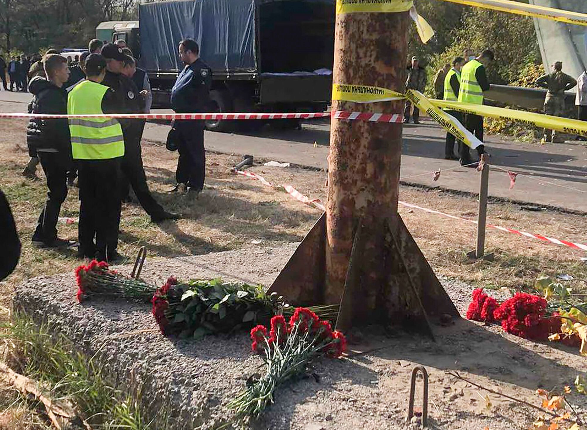 In this photo provided by the Emergency Situation Ministry, flowers lay at the scene where the AN-26 military plane crashed o