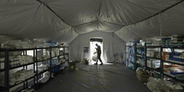 In this March 31, photo a U.S. Army soldier walks inside a mobile surgical unit being set up by soldiers from Fort Carson, Col., and Joint Base Lewis-McChord (JBLM) as part of a field hospital inside CenturyLink Field Event Center, in Seattle. Military suicides have increased by as much as 20% this year compared to the same period last year, and some incidents of violent behavior have spiked, as service members struggle with isolation and other impacts of COVID-19 added to the pressures of war-zone deployments and responding to national disasters and civil unrest. (AP Photo/Elaine Thompson, File)