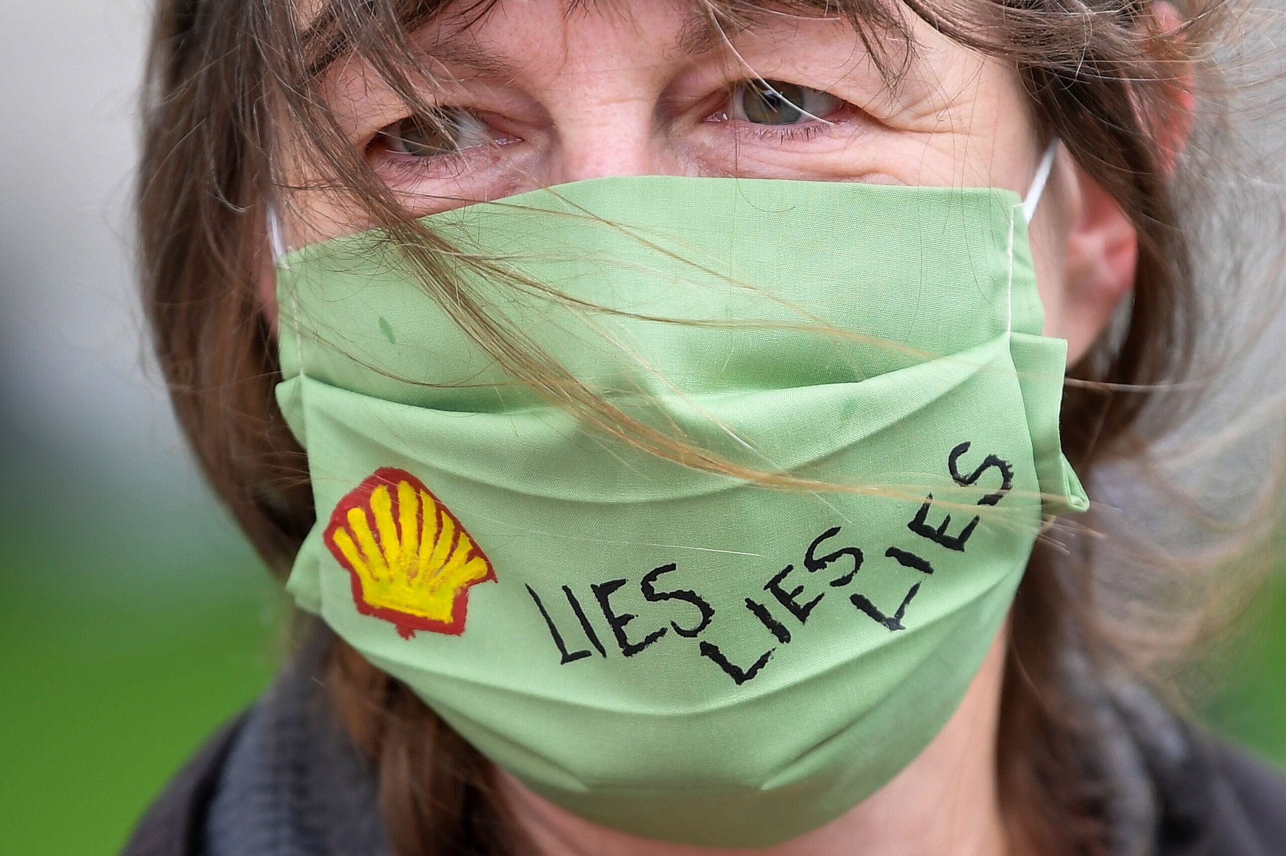 A slogan is seen on a protective face mask of an Extinction Rebellion climate action group protester as she demonstrates agai