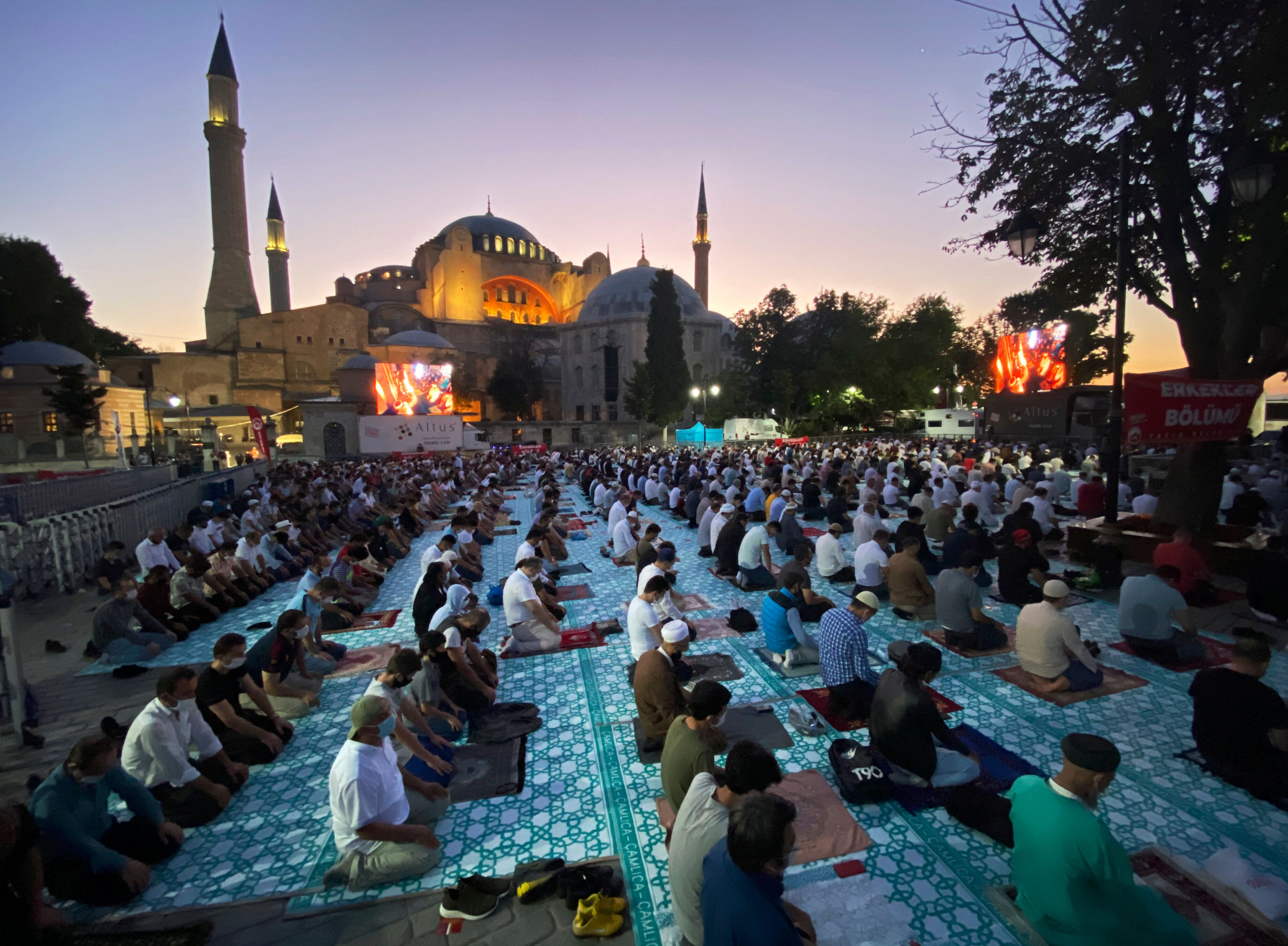 Muslims offer prayers during Eid al-Adha near the Hagia Sophia, recently converted back to a mosque, in Istanbul on July 31,