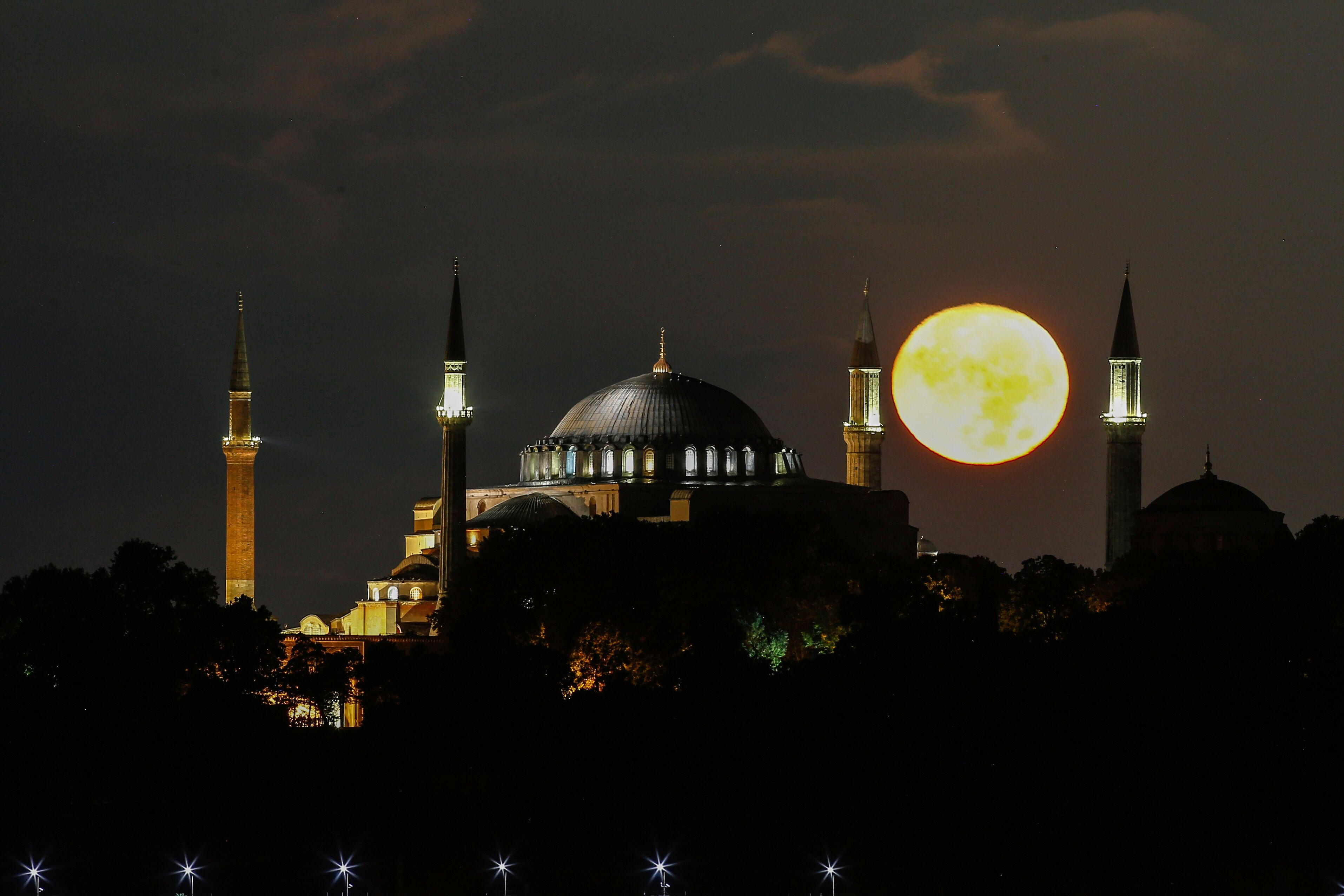 The full moon rises behind the Byzantine-era Hagia Sophia, in the historic Sultanahmet district of Istanbul, early Tuesday, S
