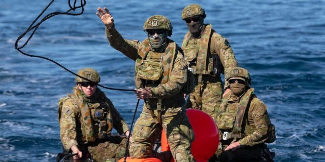 In this Sept. 25, 2020, photo provided by the Royal Australian Navy, members of the Australian Clearance Diving Team One return to Lord Howe Island, Australia, from Elizabeth Reef on a Zodiac inflatable boat following a successful search for unexploded ordnance. The 45-kilogram (100-pound) bomb was found by a fisherman on Elizabeth Reef near Lord Howe Island, about 550 kilometers (340 miles) off New South Wales state. (ABIS Sittichai Sakonpoonpol/Royal Australian Navy via AP)