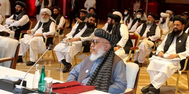 In this Sept. 12, 2020, file photo, Taliban negotiator Abbas Stanikzai, center front, and his delegation attend the opening session of peace talks between the Afghan government and the Taliban, in Doha, Qatar. (AP Photo/Hussein Sayed, File)