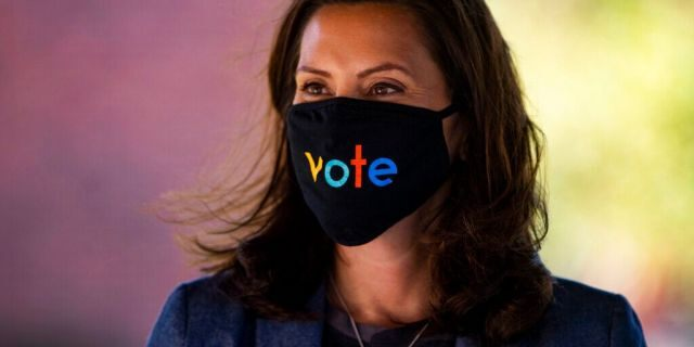 """Michigan Gov. Gretchen Whitmer wears a mask with the word """"vote"""" displayed on the front during a roundtable discussion on healthcare, Wednesday Oct. 7, 2020, in Kalamazoo, Mich."""