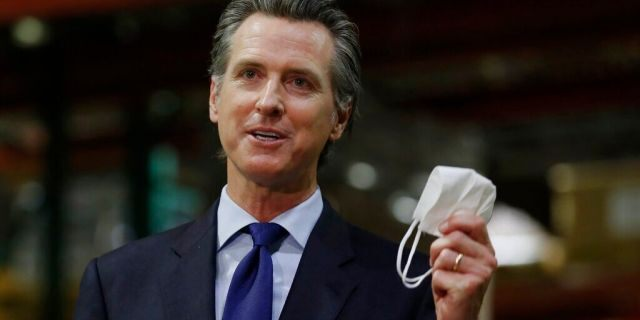 In this June 26, 2020 file photo, Gov. Gavin Newsom holds a face mask as he urges people to wear them to fight the spread of the coronavirus during a news conference in Rancho Cordova, Calif. (AP Photo/Rich Pedroncelli, Pool, File)