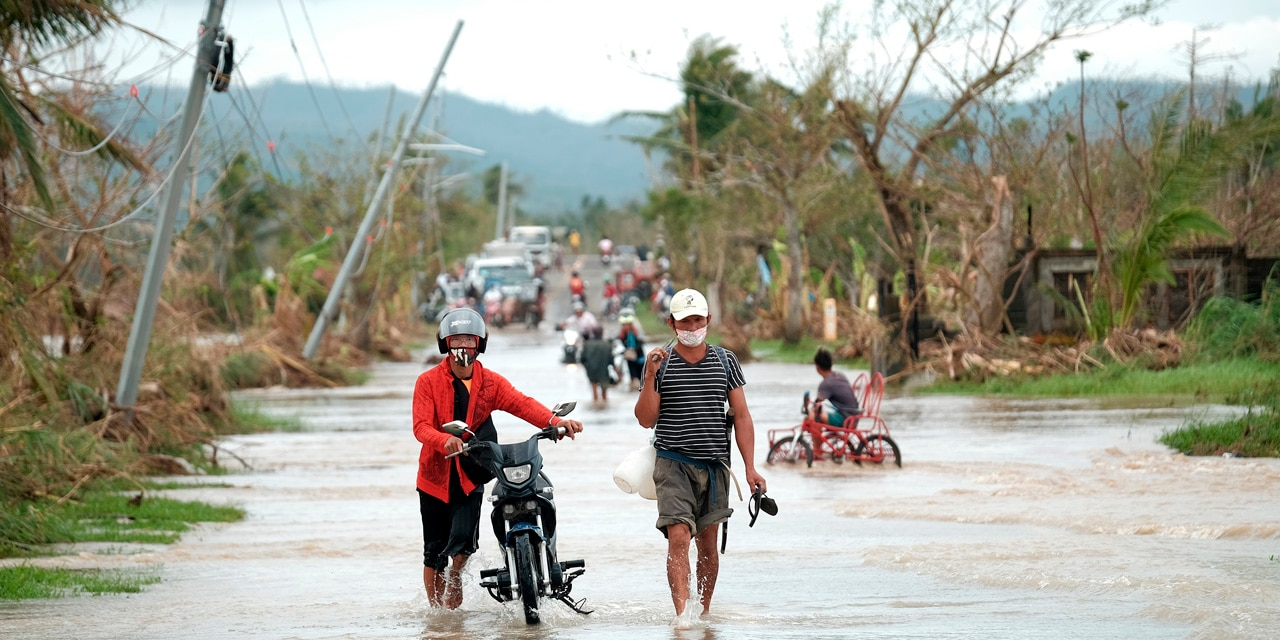 Residents walk past toppled electric posts along a flooded road in Albay province, central Philippines, due to Typhoon Vamco on Thursday, Nov. 12, 2020.