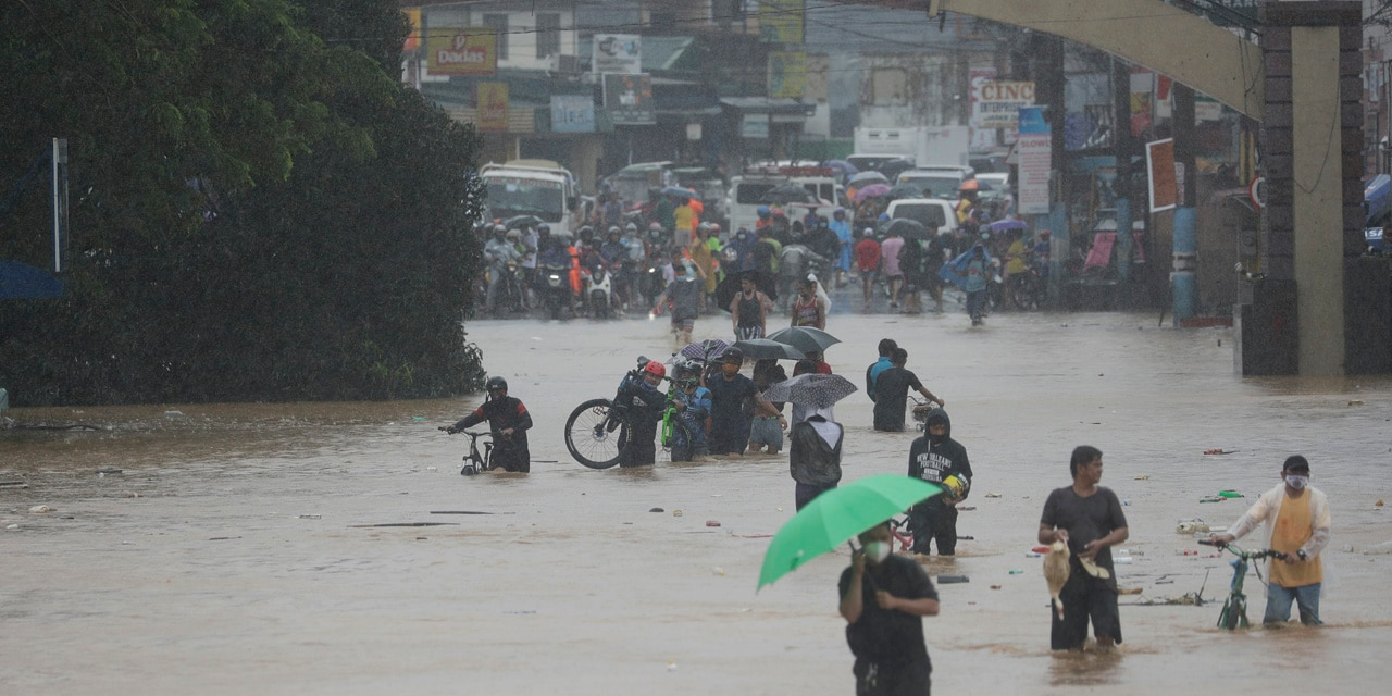 Residents walk along a flooded road in Marikina, Philippines, due to Typhoon Vamco on Thursday, Nov. 12, 2020.