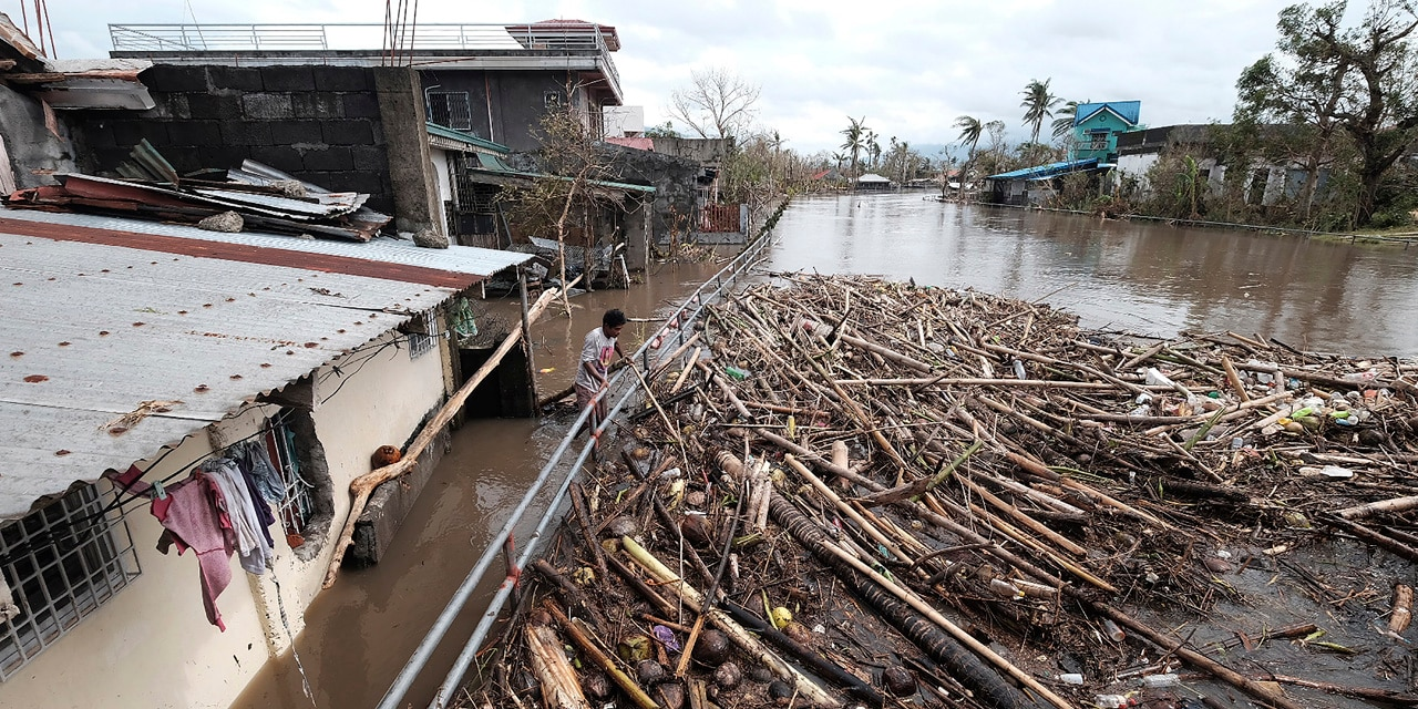 A man looks at the garbage that was washed away due to Typhoon Vamco as floods inundate villages in Legazpi, Philippines, on Thursday, Nov. 12, 2020.