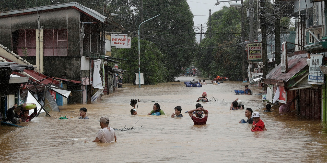Residents negotiate a flooded road as floods continue to rise in Marikina, Philippines, due to Typhoon Vamco on Thursday, Nov. 12, 2020.