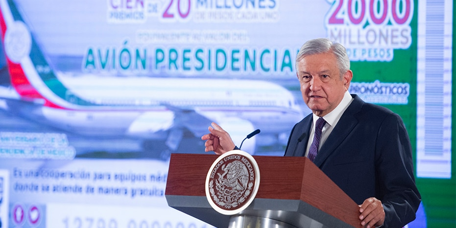 """President Andres Manuel Lopez Obrador stands in front of an image of a raffle ticket featuring the presidential plane, in his morning press conference at the National Palace in Mexico City, on Feb. 7, 2020. Lopez Obrador announced that the raffle of the Boeing Dreamliner will be symbolic, awarding total prize money of $100 million, which lottery tickets state is """"equivalent to the value of the presidential jet."""""""