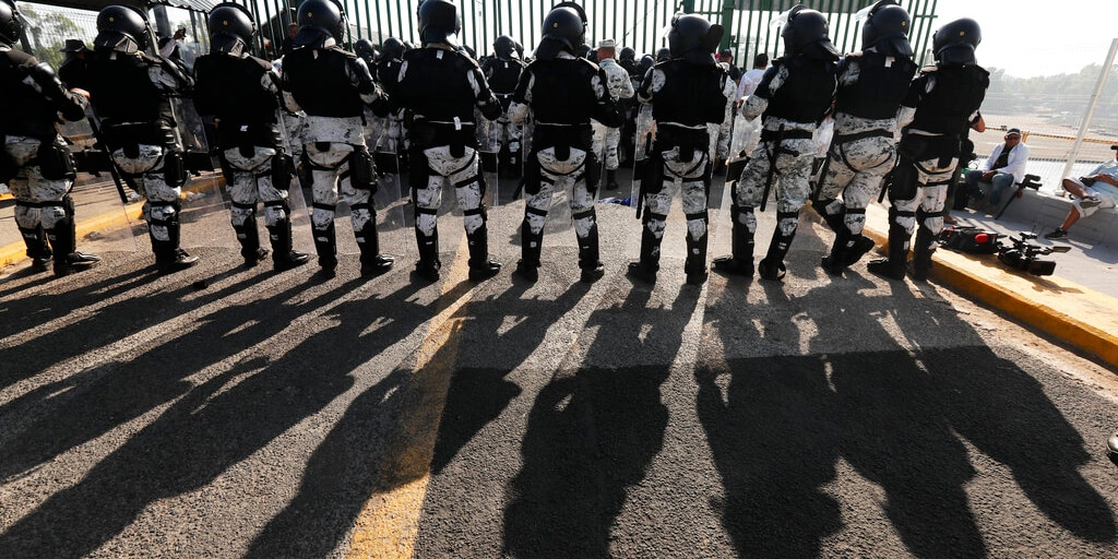 Mexican National Guardsmen block the border crossing between Guatemala and Mexico in Tecun Uman, Guatemala, Saturday, Jan. 18, 2020. More than a thousand Central American migrants surged onto the bridge spanning the Suchiate River, that marks the border between both countries, as Mexican security forces attempted to impede their journey north. (AP Photo/Marco Ugarte)