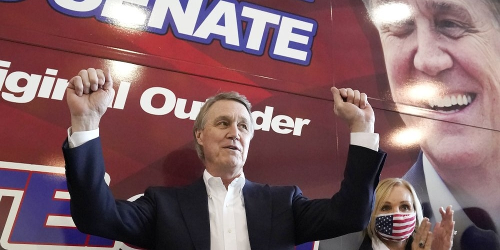 In this Nov. 2, 2020 photo, Republican candidate for Senate Sen. David Perdue and his wife Bonnie reacts during a campaign stop at Peachtree Dekalb Airport in Atlanta. Republicans are flooding Georgia with cash and field operatives as they look to keep Democrats from seizing control of the Senate under President-elect Joe Biden's administration. The Republican National Committee says it is funding more than 600 staffers in the state with an investment of at least $20 million ahead of the Jan. 5 runoffs for the seats held by GOP Sens. Kelly Loeffler and David Perdue. (AP Photo/John Bazemore)