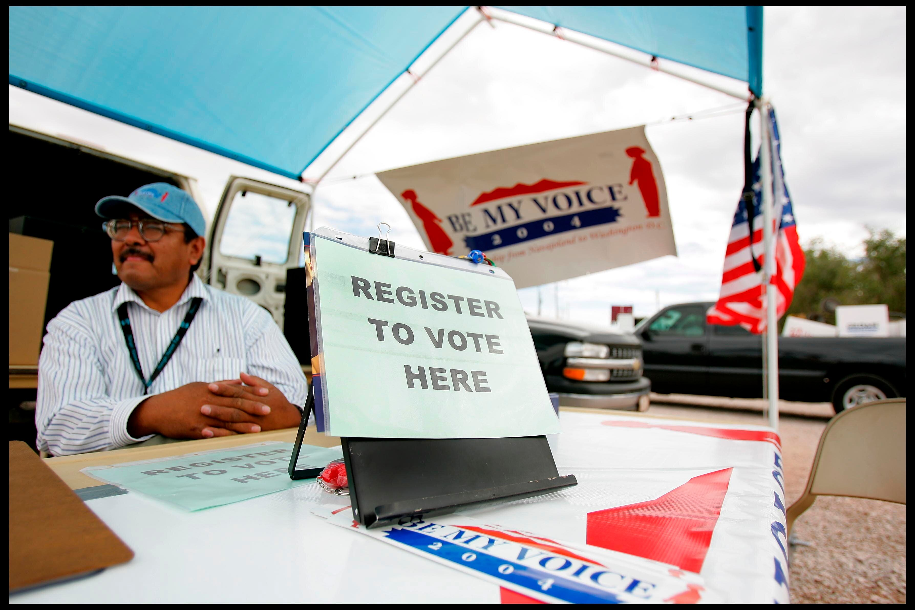 "Wilson Deschine sits at the ""be my voice"" voter registration stand at the Navajo Nation annual rodeo in Window Rock, Arizona."