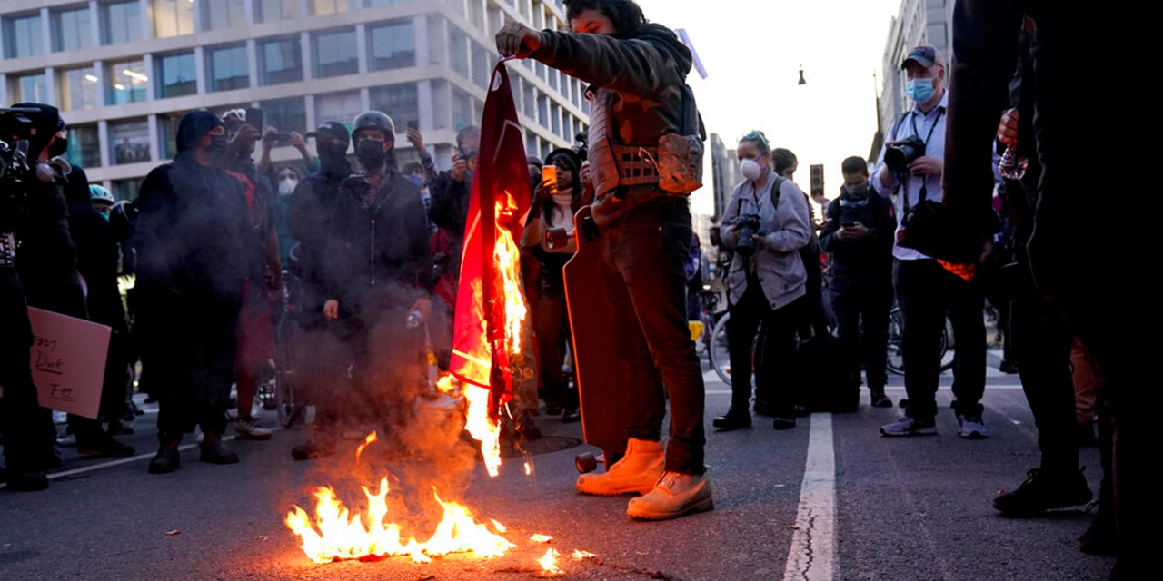 A counterprotester burns a Trump 2020 flag after supporters of President Donald Trump held pro-Trump marches Nov. 14,  in Washington. (Associated Press)