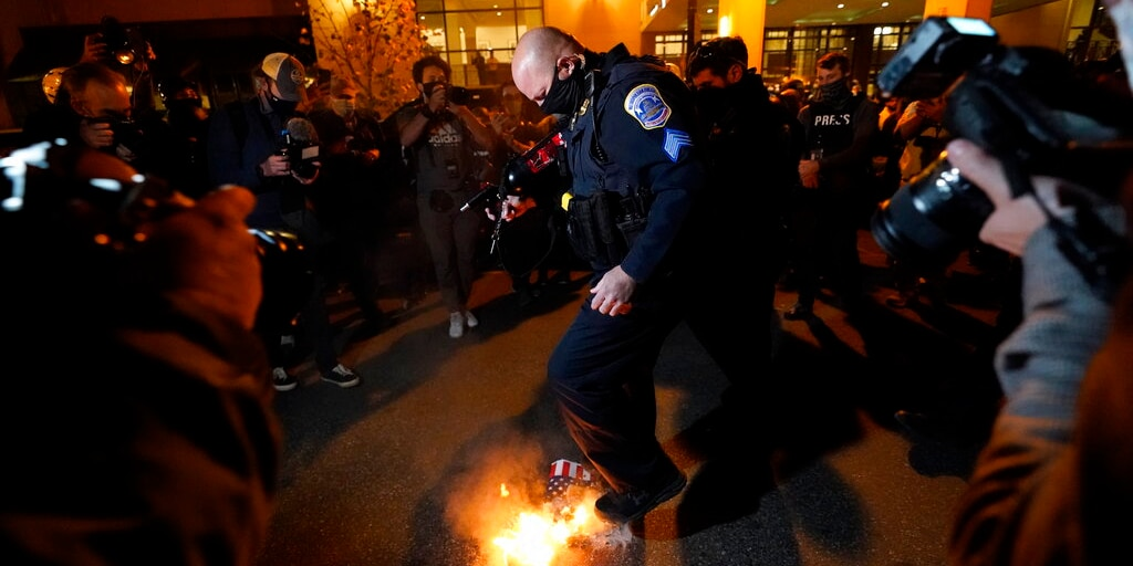 An officer puts out a sign that counter-protesters lit on fire after supporters of President Donald Trump held pro-Trump marches Nov. 14, in Washington. (AP Photo/Julio Cortez)