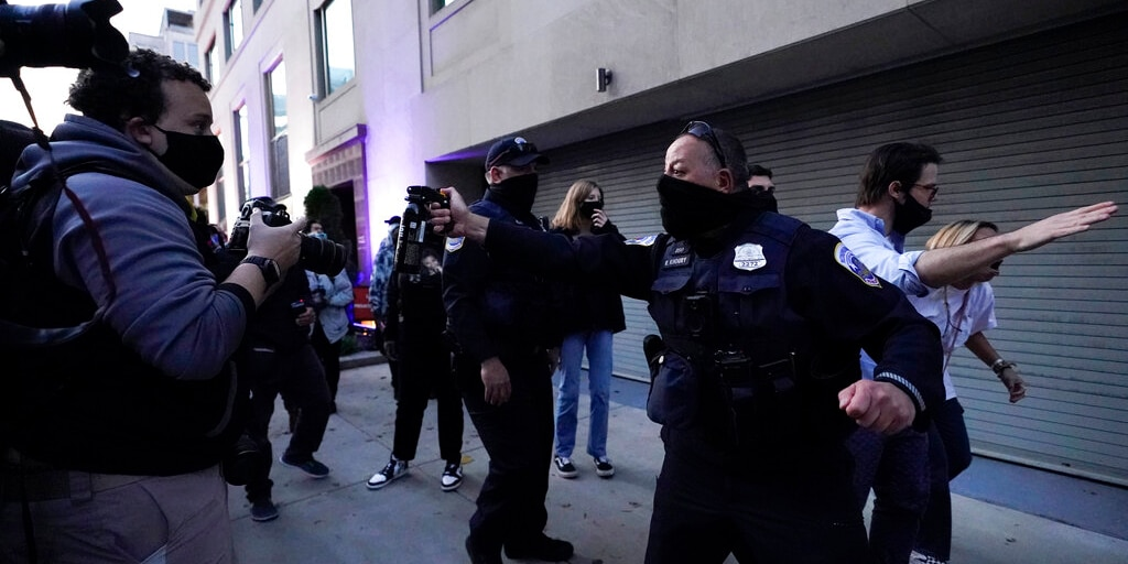 A police officer threatens to use pepper spray as they help a woman leave the counter-protester area after supporters of President Donald Trump held marches Nov. 14, in Washington. (AP Photo/Julio Cortez)