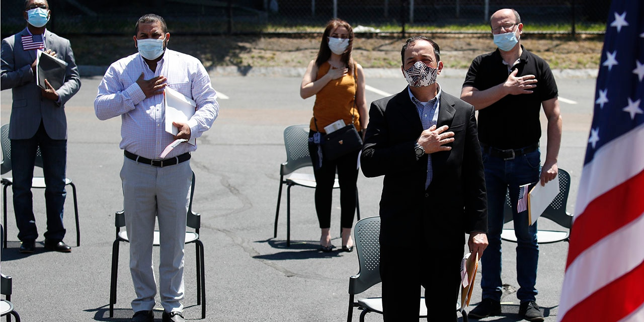 <br> New U.S. citizens, socially distanced, recite the Pledge of Allegiance outside the U.S. Citizenship and Immigration Services building in Lawrence, Mass., June 4, 2020. (Associated Press)