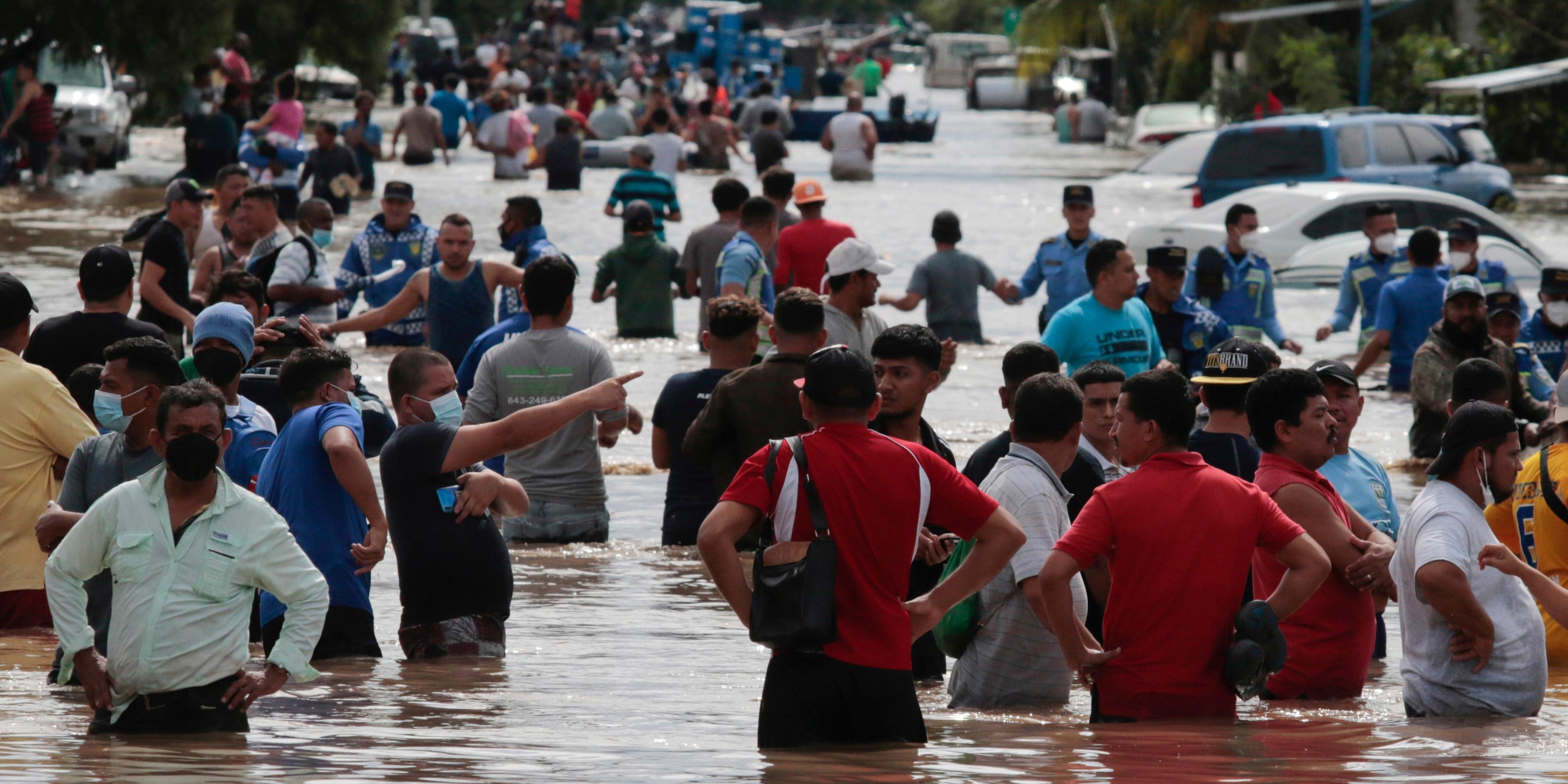 Residents wade through a flooded road in the aftermath of Hurricane Eta in Planeta, Honduras, on Nov. 5, 2020.