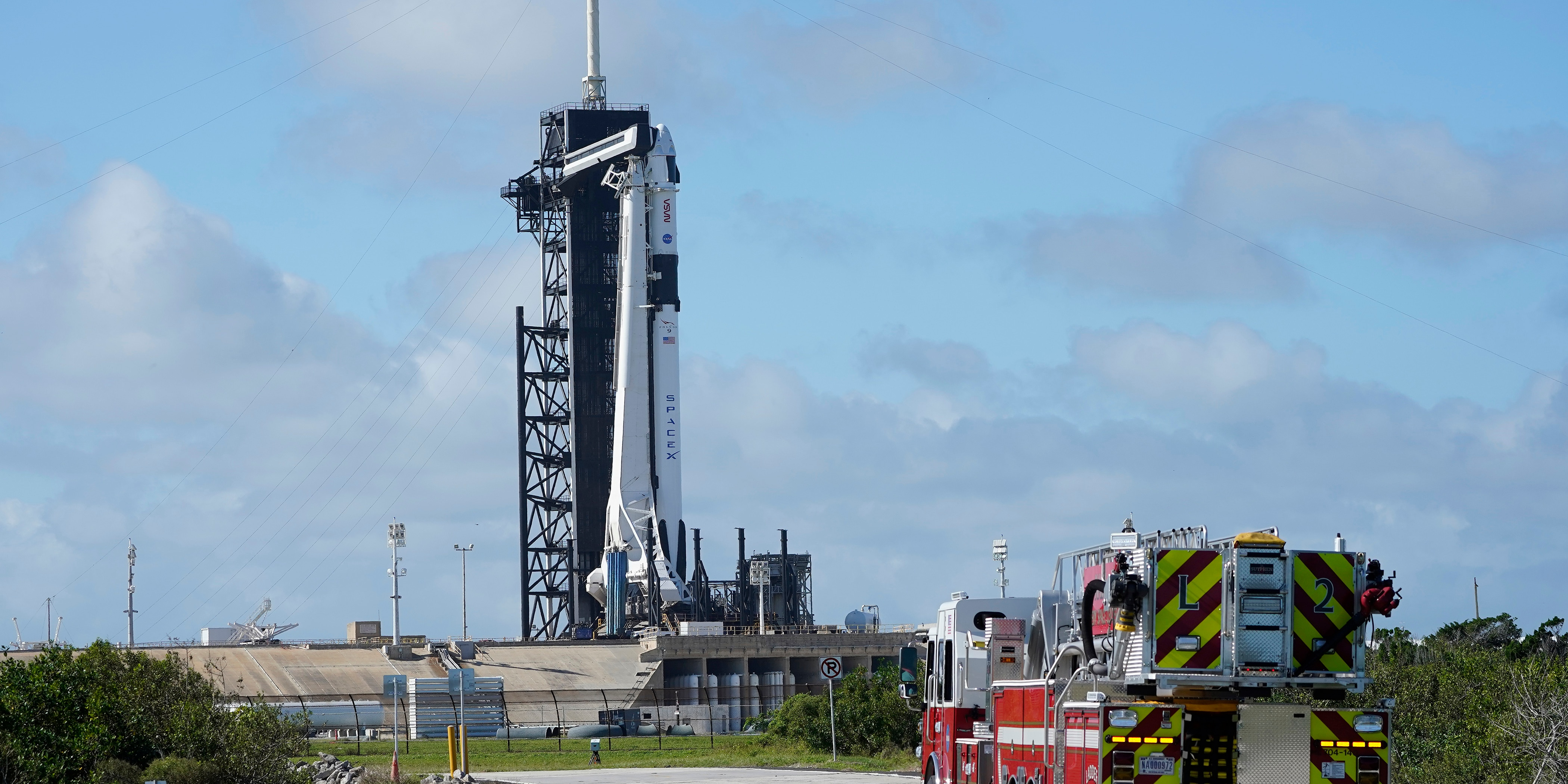 NASA firefighters drive on the road outside the fence near a SpaceX Falcon 9 rocket, with the company's Crew Dragon capsule attached, sits on the launch pad at Launch Complex 39A Friday, Nov. 13, 2020, at the Kennedy Space Center in Cape Canaveral, Fla.