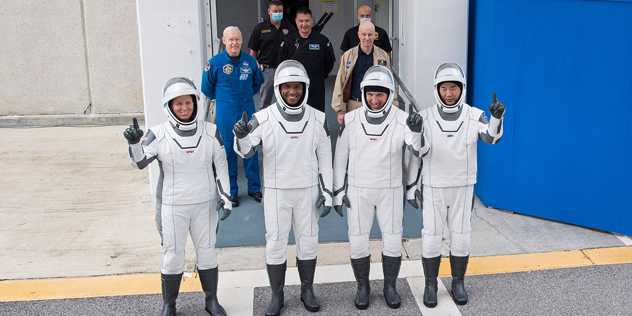 NASA astronauts, from left, Shannon Walker, Victor Glover, Mike Hopkins and Japan Aerospace Exploration Agency (JAXA) astronaut Soichi Noguchi, right, wearing SpaceX spacesuits, stop to pose for a picture as walk out of the Neil A. Armstrong Operations and Checkout Building to depart for Launch Complex 39A during a dress rehearsal Thursday, Nov. 12, 2020, at NASA's Kennedy Space Center in Cape Canaveral, Fla.