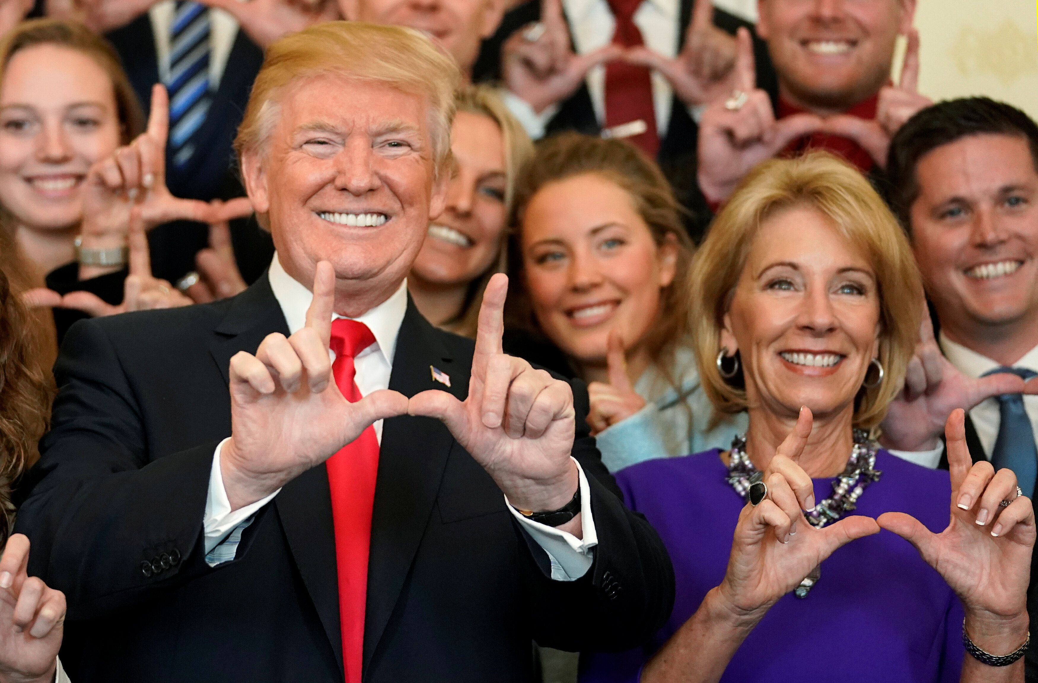 """President Donald Trump and DeVos make """"U"""" symbols with their hands while posing with the Utah Skiing team as they greet membe"""