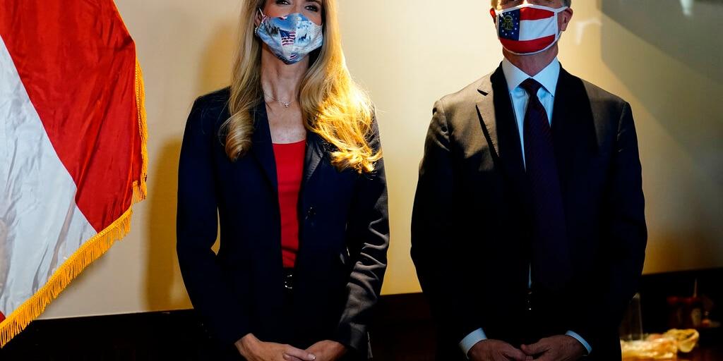 Republican candidates for U.S. Senate Sen. Kelly Loeffler, left, and Sen. David Perdue wait to speak at a campaign rally on Friday, Nov. 13, 2020, in Cumming, Ga. (AP Photo/Brynn Anderson)