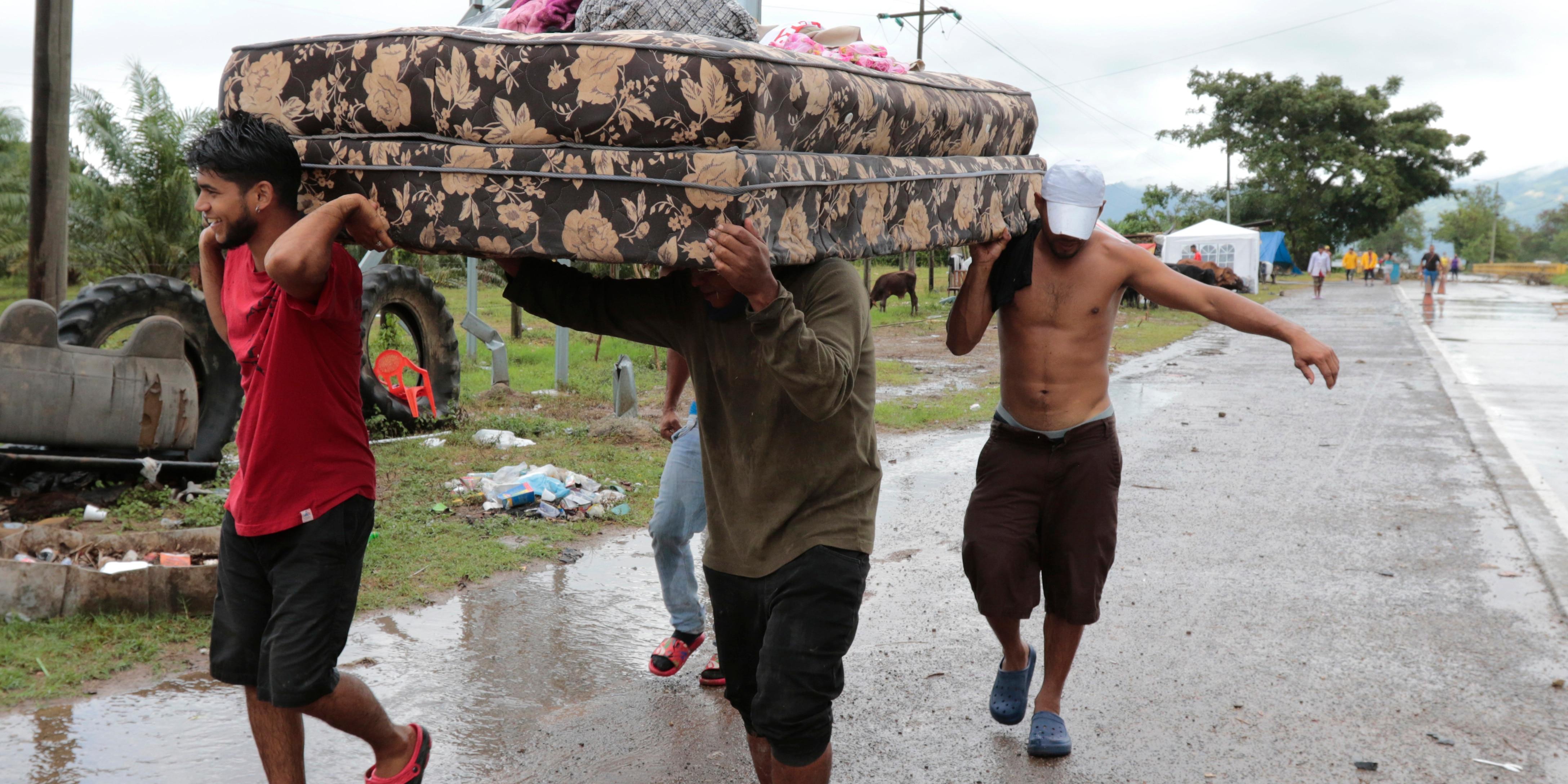 Neighbors help each other as they evacuate the area before Hurricane Iota makes landfall in San Manuel Cortes, Honduras, Monday, November 16, 2020.