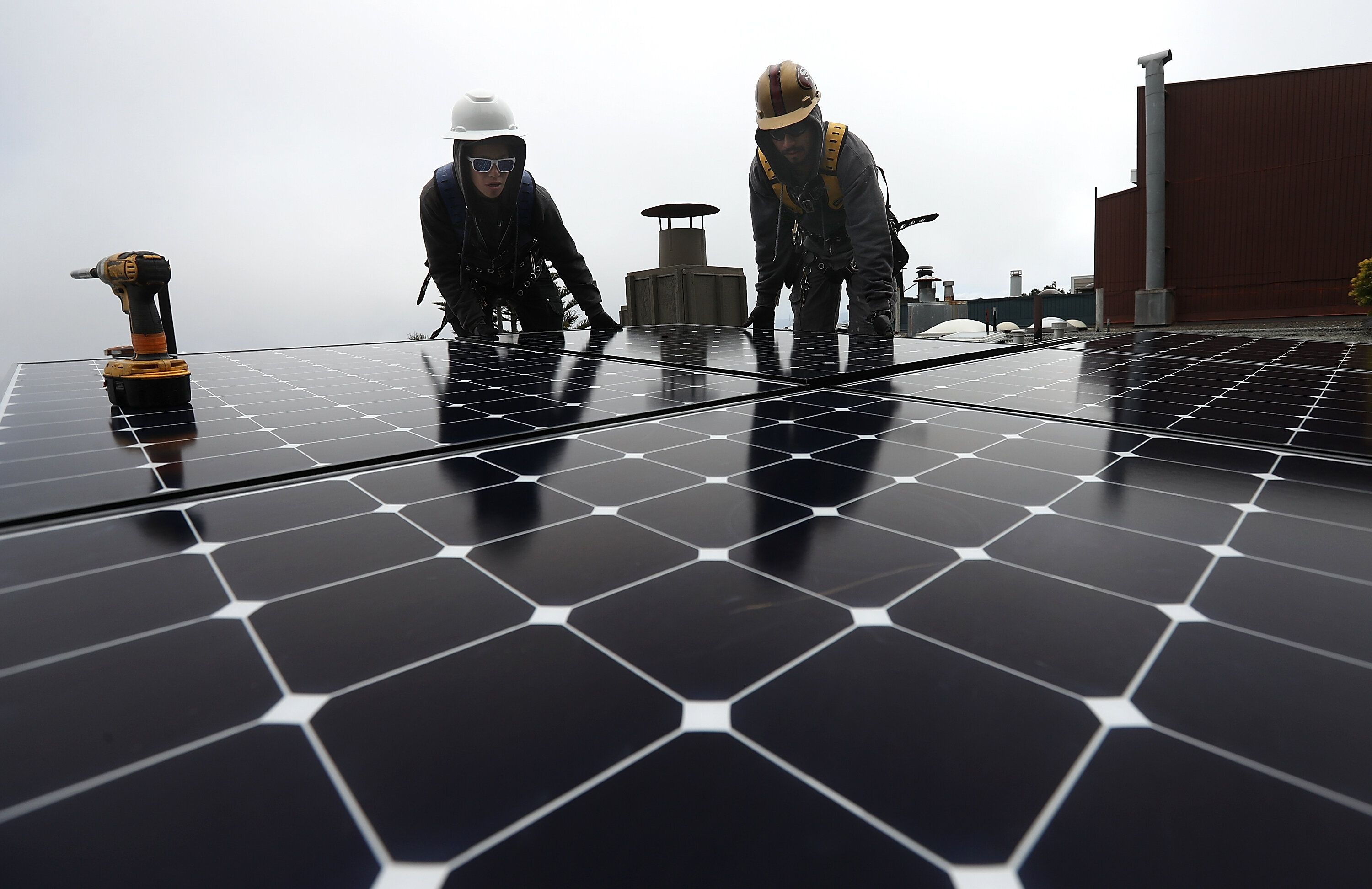 Luminalt solar installers Pam Quan and Walter Morales install solar panels on the roof of a home in San Francisco.