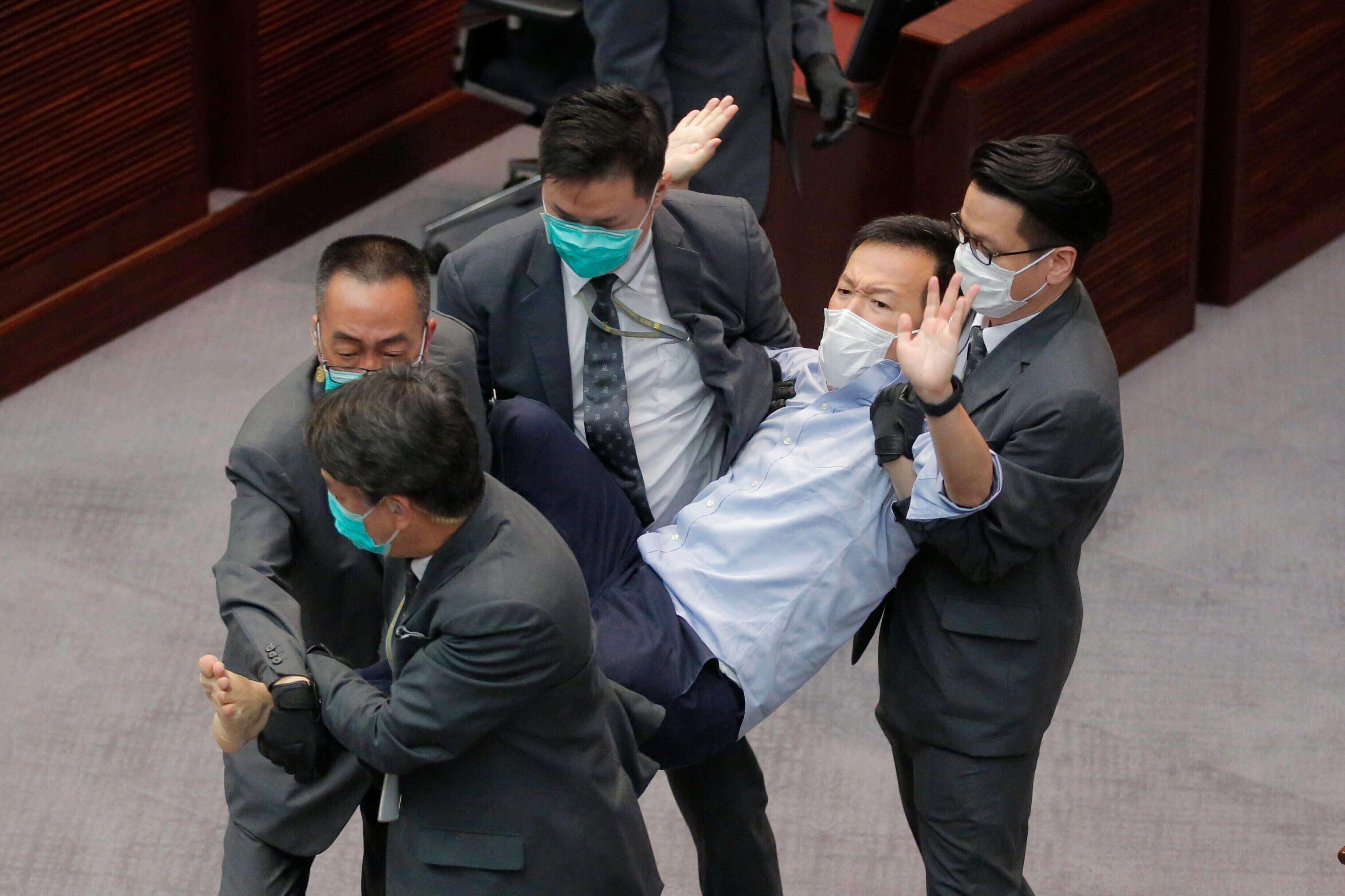 Pan-democratic legislator Raymond Chan Chi-chuen is taken away by security guards during a Legislative Council's House Commit