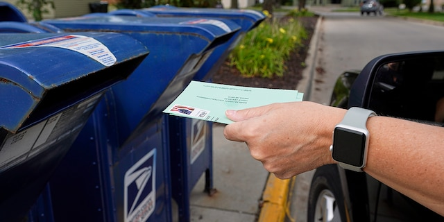 A person drops applications for mail-in-ballots into a mailbox in Omaha, Neb. (AP Photo/Nati Harnik, File)