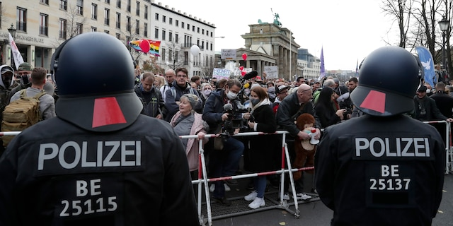 Police officers block a road between the Brandenburg Gate and the Reichstag building, home of the German federal parliament, as people attend a protest rally in front of the Brandenburg Gate in Berlin, Germany, Wednesday, Nov. 18, 2020 against the coronavirus restrictions in Germany. (AP Photo/Michael Sohn)