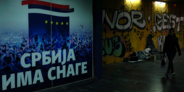 """A woman walks through an underground passage by a homeless person and inscription on the wall reading """"Serbia has the strength"""" in Belgrade, Serbia, Monday, Nov. 16, 2020."""