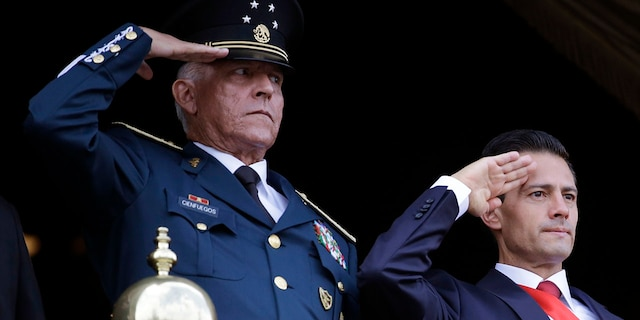 In this Sept. 16, 2016 file photo, Defense Secretary Gen. Salvador Cienfuegos, left, and Mexico's President Enrique Pena Nieto, salute during the annual Independence Day military parade in Mexico City's main square. (AP Photo/Rebecca Blackwell, File)