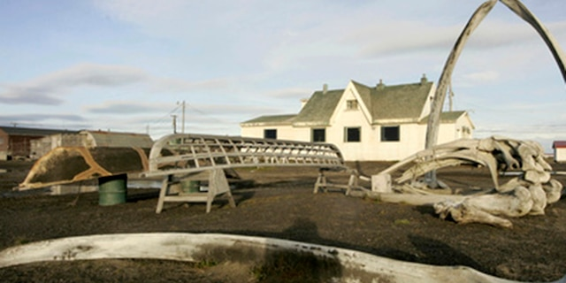 In this Aug. 12, 2005, file photo, a skin boat display sits next to whale bones and an arch made of a whale jaw on the beach at Brower's Cafe in Barrow, Alaska.