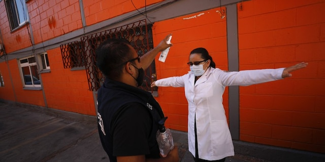 <br> Dr. Monserrat Castaneda is sprayed with a disinfectant after conducting a COVID-19 test inside a home, in the Venustiano Carranza borough of Mexico City, Thursday, Nov. 19, 2020. (AP Photo/Rebecca Blackwell)