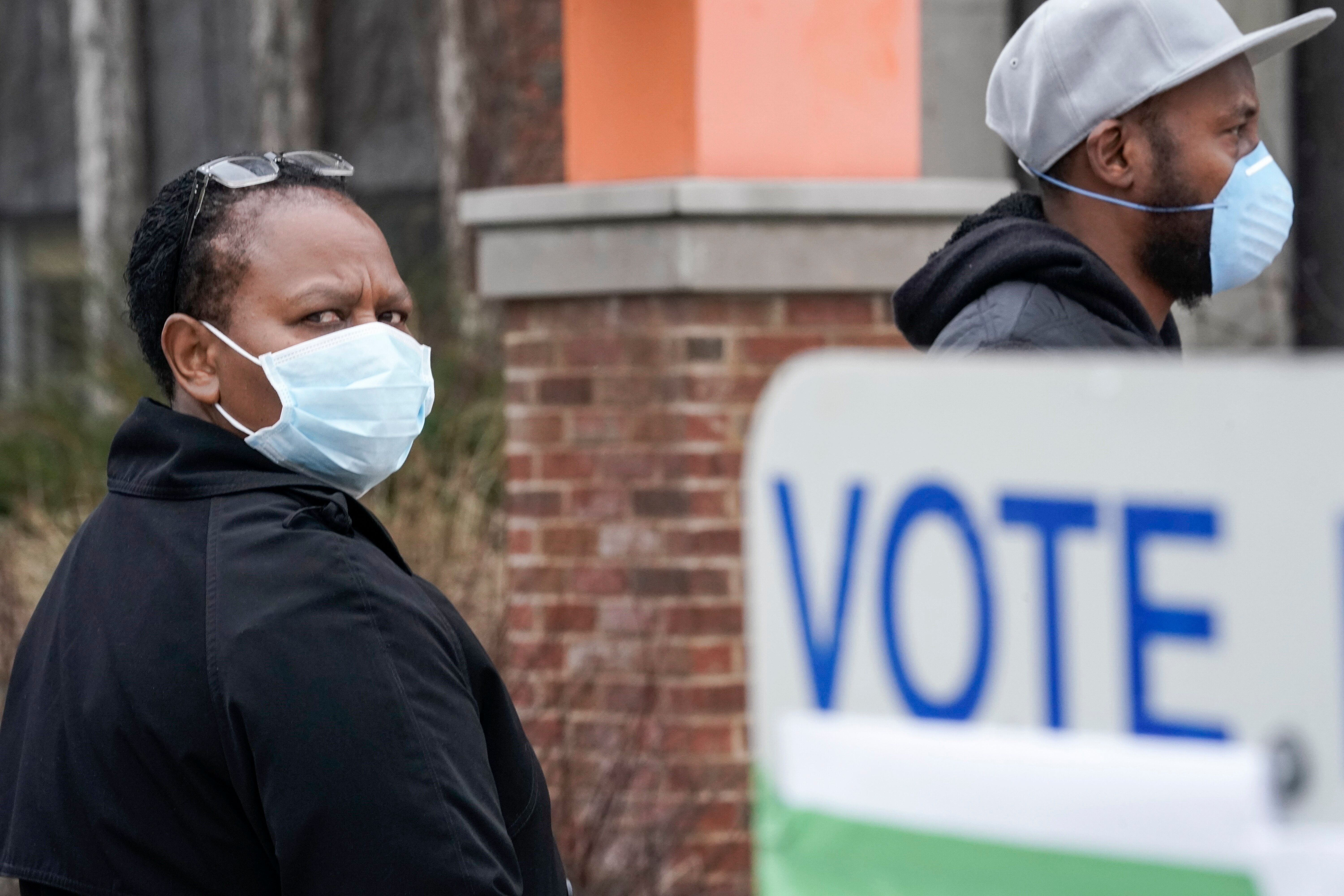 Voters masked against the coronavirus line up to vote at Riverside High School in Milwaukee.