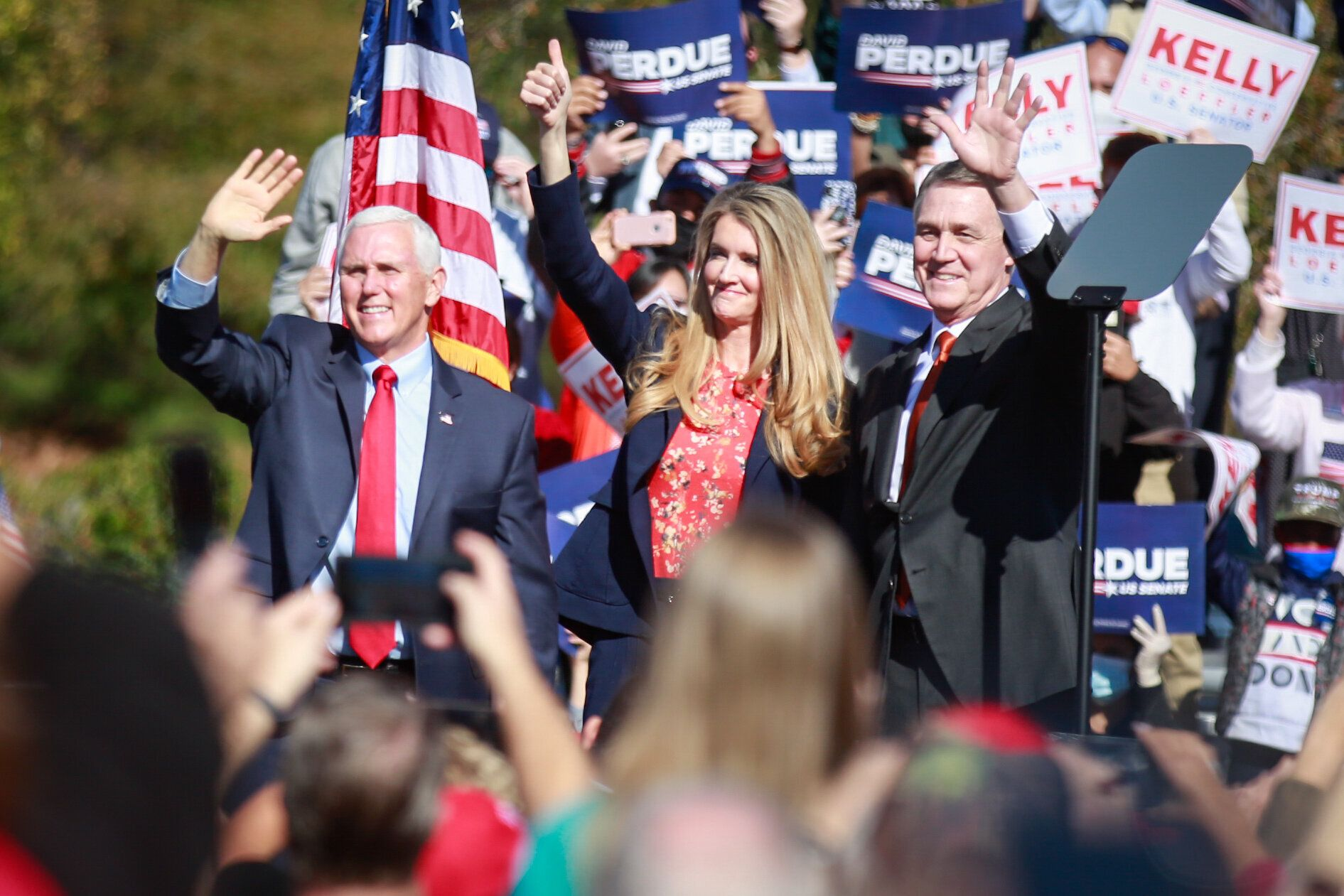 Vice President Mike Pence (from left) and Sens. Kelly Loeffler and David Perdue wave to supporters at a Defend the Majority R