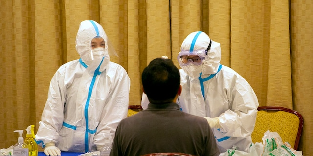 Workers in protective suits administer a COVID-19 test in Wenchang in southern China's Hainan Province on Sunday. (AP Photo/Mark Schiefelbein)