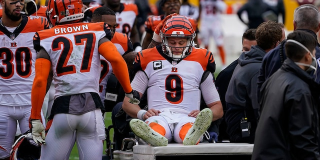 Cincinnati Bengals quarterback Joe Burrow (9) is consoled by teammates as he is carted off the field during the second half of an NFL football game against the Washington Football Team, Sunday, Nov. 22, 2020, in Landover. Burrow was carted off the field with a left knee injury. (AP Photo/Susan Walsh)