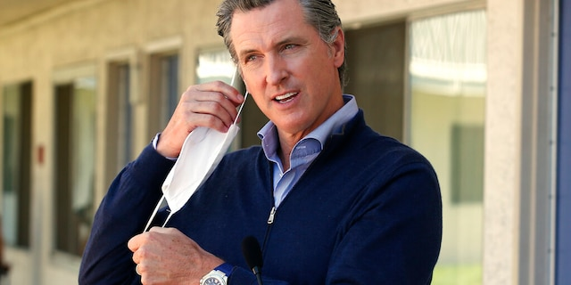 Gov. Gavin Newsom removes his face mask before giving an update during a visit to Pittsburg, Calif on June 30, 2020. (AP Photo/Rich Pedroncelli, Pool, File)