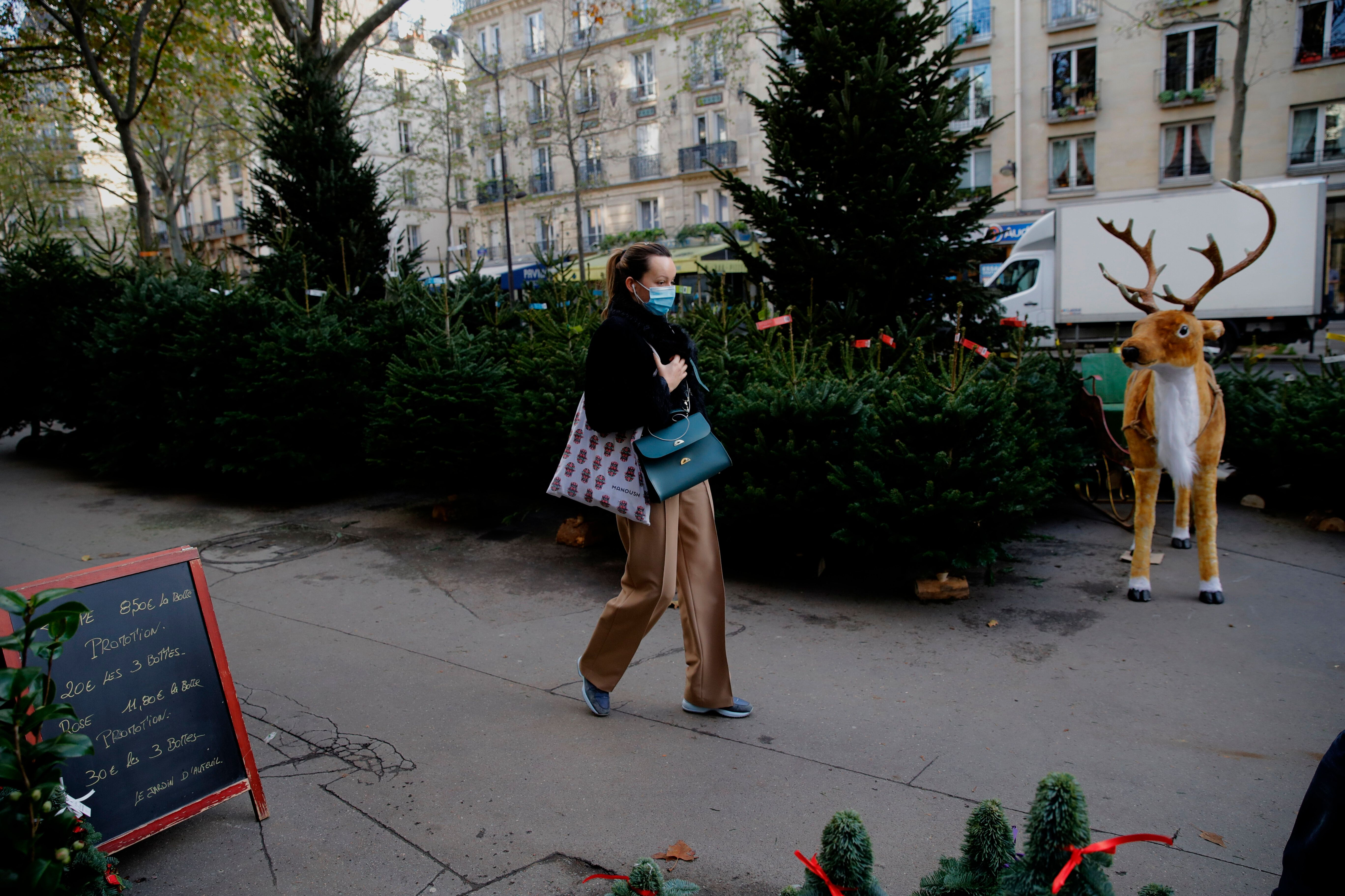 A woman walks past Christmas trees at florist in Paris on Friday. The number of new coronavirus infections in France rose by
