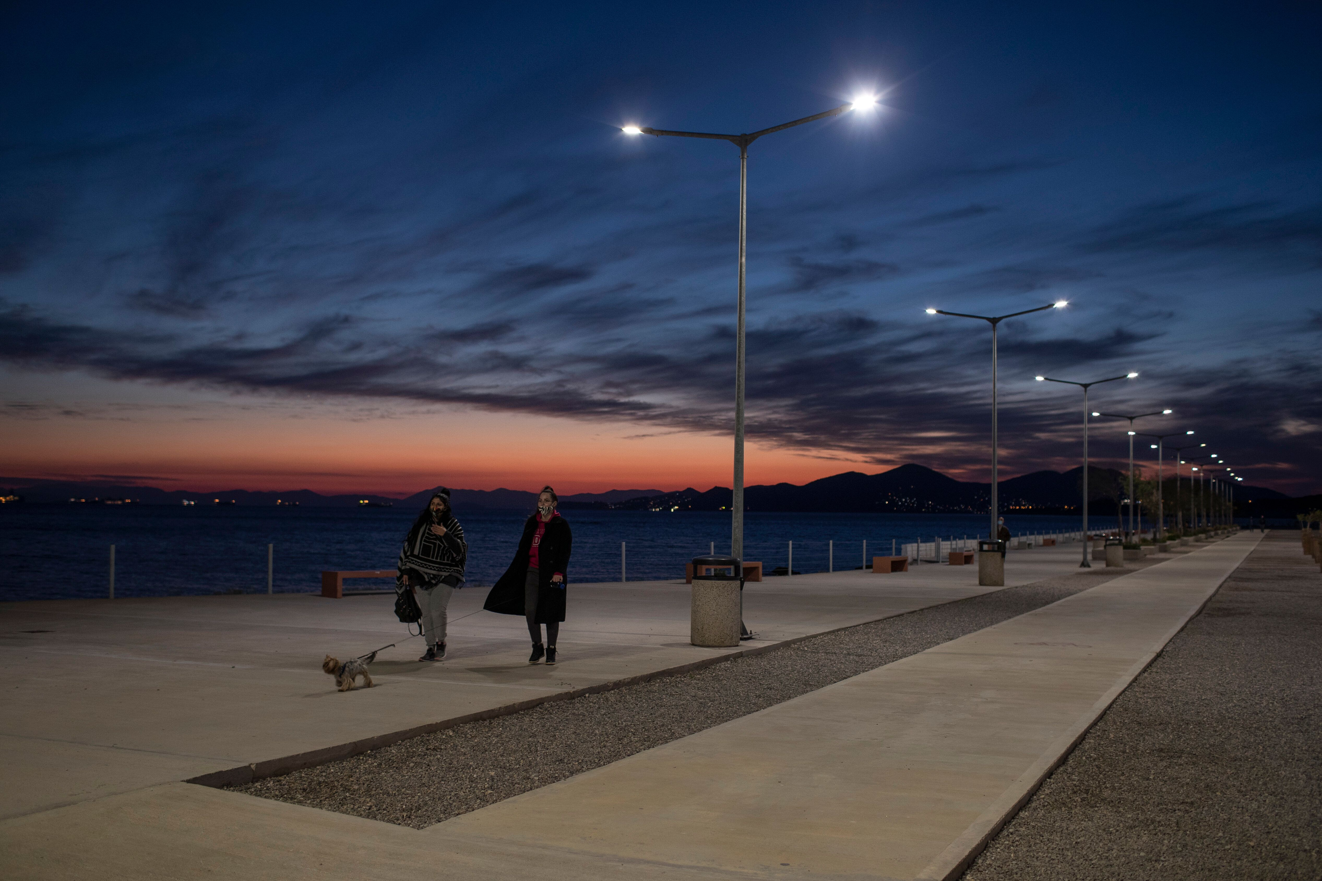 People walk by the seain Drapetsona suburb of Piraeus, near Athens, on Monday. A second nationwide lockdown is in place until