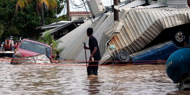 FILE: A resident walking through a flooded street looks back at storm damage caused by Hurricane Eta in Planeta, Honduras.
