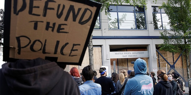 """A protester holds a sign that reads """"defund the police"""" after Seattle Police vacated the department's East Precinct and people continue to rally against racial inequality and the death in Minneapolis police custody of George Floyd, in Seattle, Washington, U.S. June 8, 2020. (REUTERS/Jason Redmond)"""